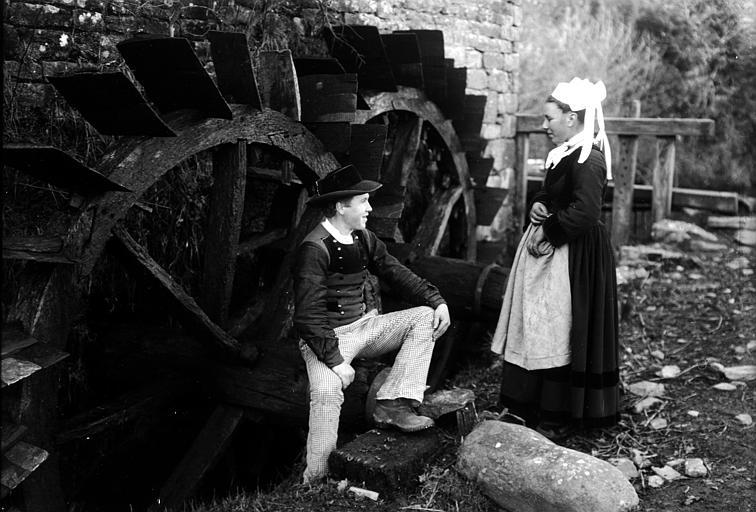 Couple en costume traditionnel : couple posant devant des roues de moulin