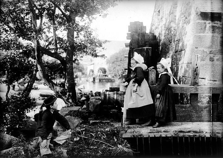 Enfants en costume traditionnel : garçon et fillettes posant devant des roues de moulin