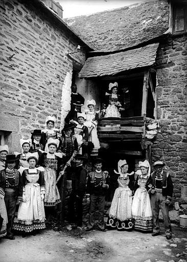 Groupe en costume traditionnel, noces (supposées) : personnes en costume de fête posant le long d'un escalier, femmes portant la coiffe 'Giz Föen' et une collerette plissée, hommes portant le 'Chupenn' (veste) et le gilet brodés