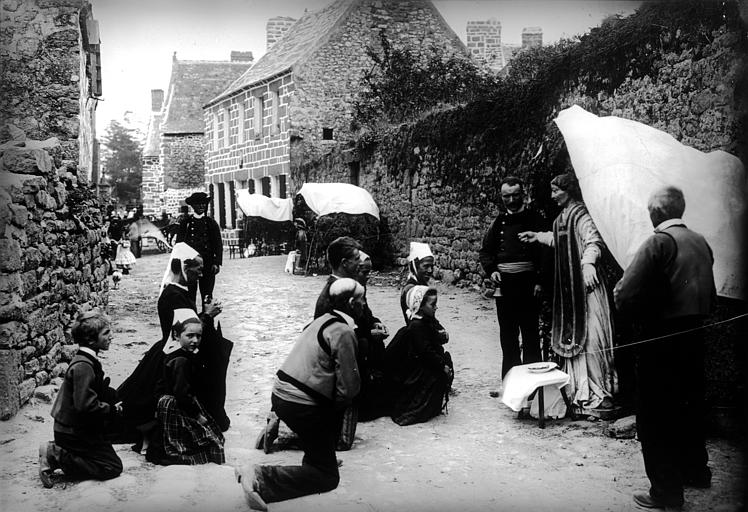 Troménie. Groupe en costume traditionnel, scène de dévotion : dans une rue, femmes portant une coiffe de Quimper, hommes et enfants agenouillés en prière devant une statue de saint