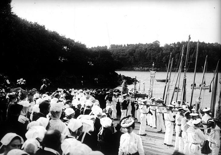 Bénédiction des bateaux : foule des pélerins en costume traditionnel assemblée le long de la berge, marins portant des ex-voto de bateaux, la bannière et les statues de la Vierge à l'Enfant, du Christ et d'un saint