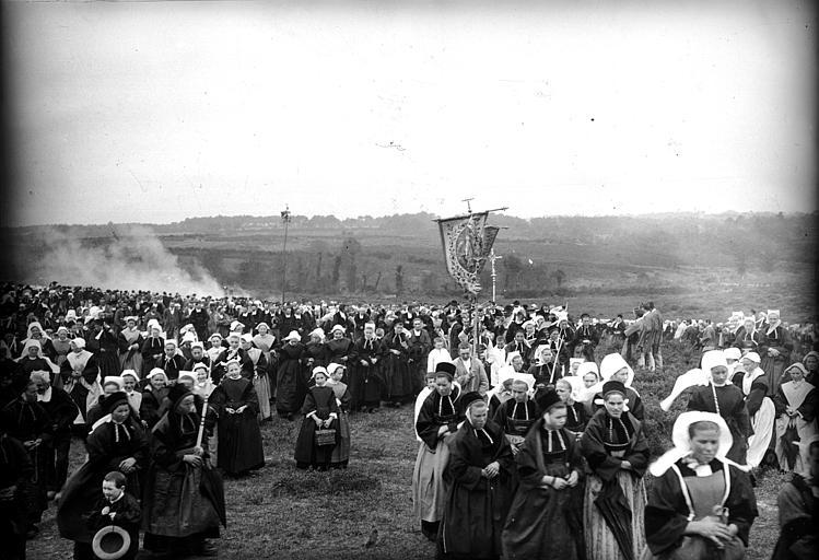 Pardon : pélerins en costume traditionnel s'acheminant vers le lieu de culte, vue d'ensemble de la procession et de la bannière