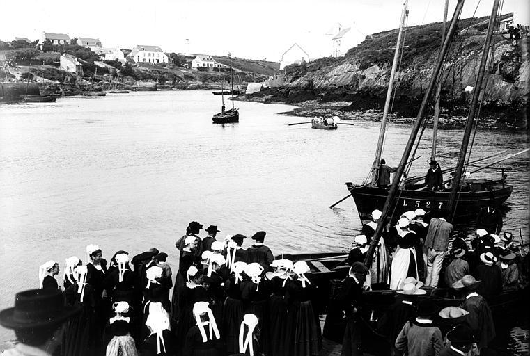 Port de pêche : groupe en costume traditionnel attendant un bateau pour l'accostage