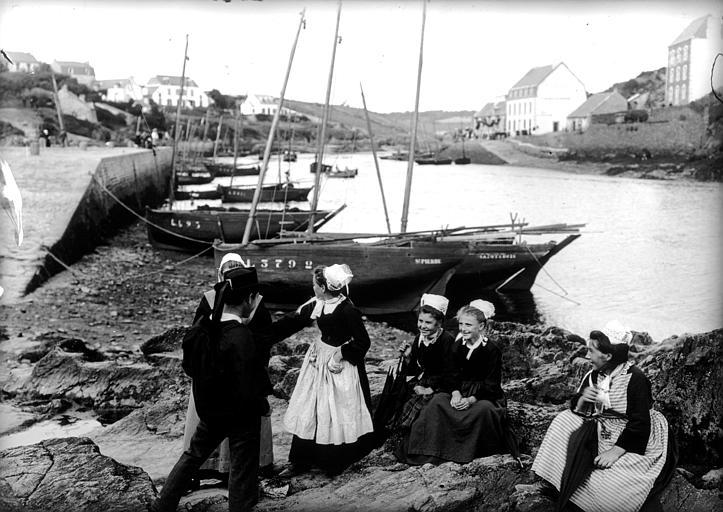 Port de pêche : groupe de jeunes gens en costume traditionnel discutant à marée basse sur la grève