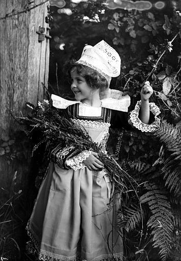 Fillette en costume traditionnel (coiffe Giz Foën et collerette plissée) posant avec un bouquet dans les bras