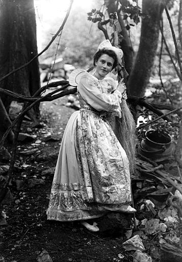 Jeune femme en costume traditionnel (coiffe Giz Foën et collerette plissée) posant adossée à une quenouille