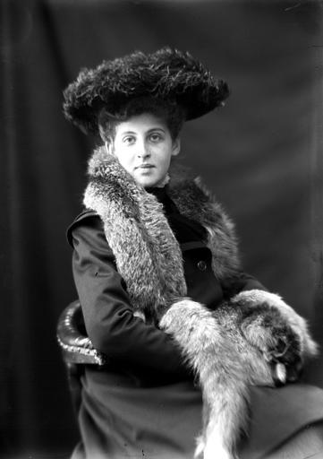 Portrait de femme assise portant une écharpe de fourrure et un chapeau en plumes d'autruche : vue de trois-quart face