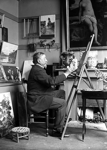 Peintre dans son atelier travaillant à une oeuvre posée sur un chevalet