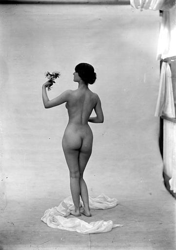 Mise en scène d'un modèle féminin nu : vu de dos, cheveux relevés en chignon, fleurs à la main