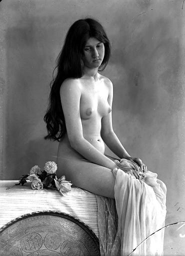 Mise en scène d'un modèle féminin nu : vu de trois-quarts face, cheveux libres sur les épaules, assise, voile sur les jambes, fleurs à côté d'elle