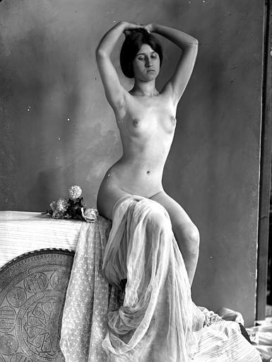 Mise en scène d'un modèle féminin nu : vu de face, cheveux relevés en chignon, assise, voile sur les jambes, fleurs à côté d'elle