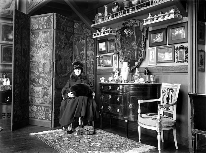 Scène d'intérieur : femme portant manteau et chapeau de fourrure assise dans un salon. Au mur photographies encadrées de Constant Puyo