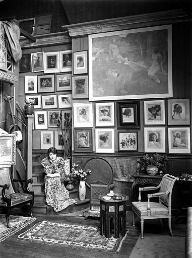 Scène d'intérieur : femme portant une robe fleurie assise dans un escalier (de face), pensive. Au mur photographies encadrées de Constant Puyo