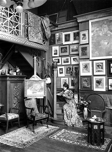 Scène d'intérieur : femme portant une robe fleurie assise dans un escalier (de trois-quart), lisant. Au mur photographies encadrées de Constant Puyo