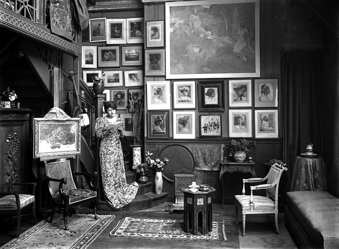 Scène d'intérieur : femme portant une robe fleurie debout dans un escalier (de trois-quart face), lisant. Au mur photographies encadrées de Constant Puyo