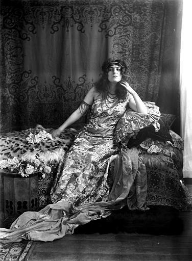 Mise en scène d'un modèle féminin : jeune femme assise sur un divan, vue de face, habillée à l'oriental, cheveux libres avec serre-tête