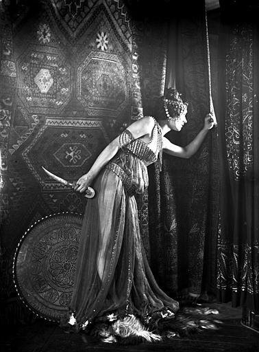 Mise en scène d'un modèle féminin : jeune femme habillée à l'oriental, un poignard dans les mains regardant au travers d'un rideau