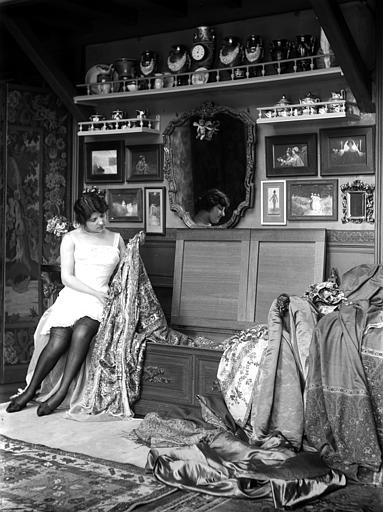 Mise en scène d'un modèle féminin : femme assise en déshabillé choisissant un vêtement dans un coffre. Au mur photographies encadrées de Constant Puyo