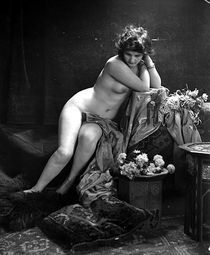 Mise en scène d'un modèle féminin : jeune femme nue assise, au milieu de bouquets de fleurs