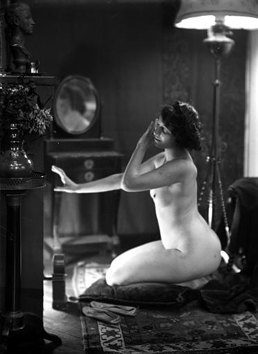 Mise en scène d'un modèle féminin : jeune femme nue assise sur un tapis, vue de profil, regardant la lumière d'un feu de cheminée