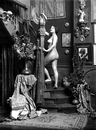 Mise en scène d'un modèle féminin : jeune femme nue montant un escalier, vue de trois-quart dos, statue de cygne posée sur le montant de la rampe d'escalier