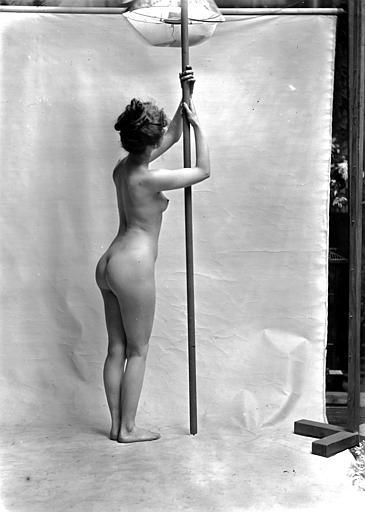 Mise en scène d'un modèle féminin : jeune femme nue, vue de trois-quart dos, se tenant à une barre verticale