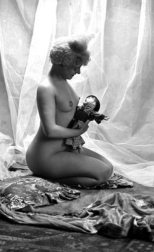 Mise en scène d'un modèle féminin : jeune femme nue, vue de profil, arborant un style de coiffure utilisé par les artistes de cirque (clowns, début 1900), assise sur des coussins et tenant une poupée dans ses bras