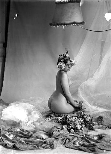 Mise en scène d'un modèle féminin : jeune femme nue, vue de trois-quarts dos, agenouillée au milieu des fleurs