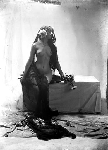 Mise en scène d'un modèle féminin : jeune femme nue, vue de trois-quart face, assise sur un coffre et portant un voile noir