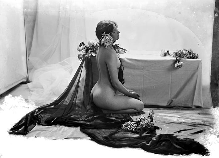 Mise en scène d'un modèle féminin : jeune femme nue, vue de trois-quart dos, assise au sol, à côté d'un coffre, le voile noir installé dans le décor