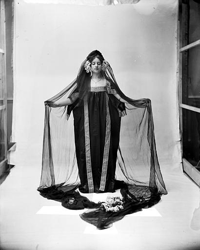 Mise en scène d'un modèle féminin : jeune femme habillée à la grecque arborant un voile noir, vue de face