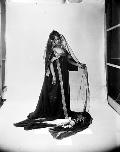 Mise en scène d'un modèle féminin : jeune femme habillée à la grecque arborant un voile noir, vue de trois-quart face