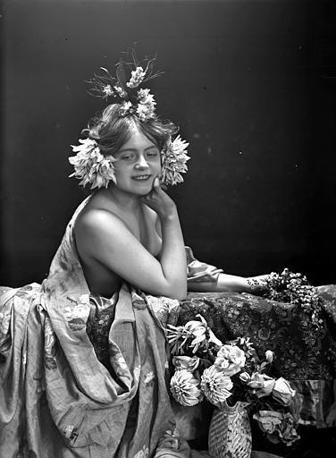 Mise en scène d'un modèle féminin : buste d'une jeune femme nue accoudée à une rambarde fleurie, vue de trois-quart face