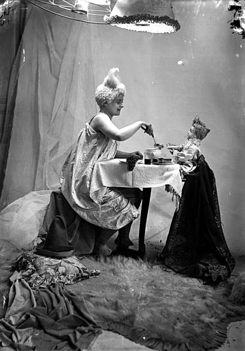 Mise en scène d'un modèle féminin : jeune femme, vue de profil, arborant un style de coiffure utilisé par les artistes de cirque (clowns, début 1900), assise autour d'une table, la poupée en face d'elle (simulation de repas)