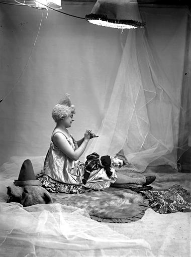 Mise en scène d'un modèle féminin : jeune femme, vue de profil, arborant un style de coiffure utilisé par les artistes de cirque (clowns, début 1900), assise sur le sol, recousant la poupée posée sur ses jambes