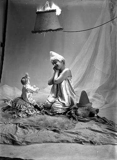 Mise en scène d'un modèle féminin : jeune femme, vue de trois-quart face, arborant un style de coiffure utilisé par les artistes de cirque (clowns, début 1900), assise sur le sol, regardant une poupée assise en face d'elle
