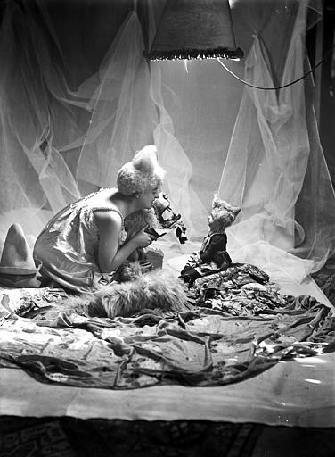 Mise en scène d'un modèle féminin : jeune femme, vue de profil, arborant un style de coiffure utilisé par les artistes de cirque (clowns, début 1900), assise sur le sol, présentant la tête d'un ours (carpette) à une poupée assise en face d'elle
