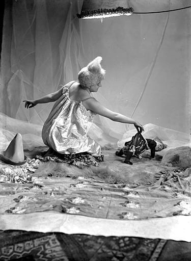 Mise en scène d'un modèle féminin : jeune femme, vue de trois-quart dos, arborant un style de coiffure utilisé par les artistes de cirque (clowns, début 1900), assise sur le sol, jouant avec une poupée
