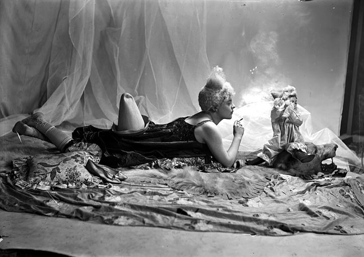 Mise en scène d'un modèle féminin : jeune femme, vue de profil, arborant un style de coiffure utilisé par les artistes de cirque (clowns, début 1900), allongée sur le sol, fumant devant une poupée