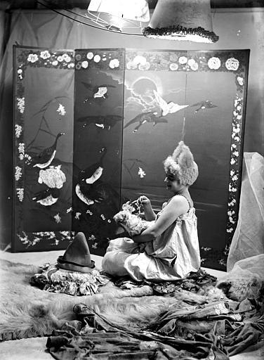 Mise en scène d'un modèle féminin : jeune femme, vue de profil, arborant un style de coiffure utilisé par les artistes de cirque (clowns, début 1900), assise sur le sol, donnant à manger à une poupée posée dans ses bras. Décor avec un paravent japonais