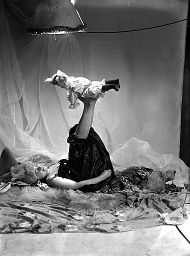 Mise en scène d'un modèle féminin : jeune femme, vue de profil, arborant un style de coiffure utilisé par les artistes de cirque (clowns, début 1900), allongée sur le sol, jambes en l'air avec une poupée posée sur ses pieds