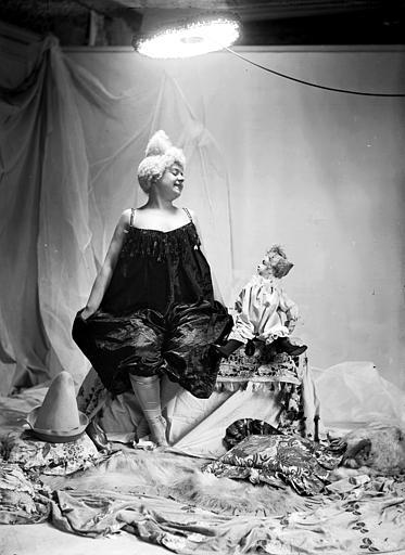 Mise en scène d'un modèle féminin : jeune femme, vue de face arborant un style de coiffure utilisé par les artistes de cirque (clowns, début 1900), assise sur un coffre avec la poupée posée à côté d'elle