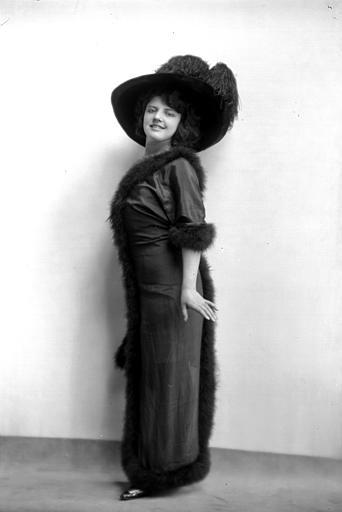 Portrait en pied d'une élégante : jeune femme en robe à bordure en fourrure et chapeau à plumes d'autruche