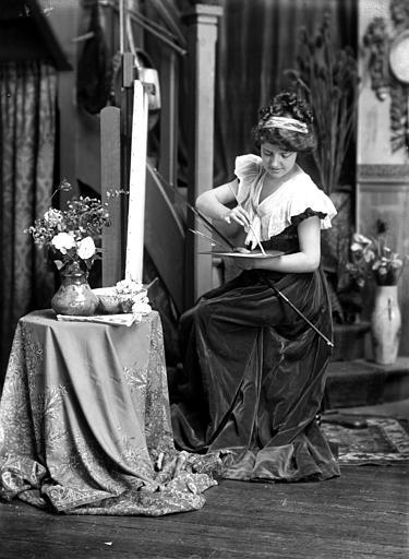 Mise en scène d'un modèle féminin, intérieur : jeune femme assise peignant devant un chevalet