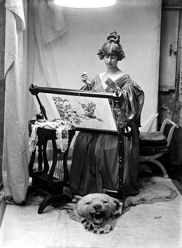 Mise en scène d'un modèle féminin, intérieur : jeune femme assise habillée à la manière du style Louis-Philippe faisant de la tapisserie, de face, mobilier de la scène organisé sur une peau d'ours