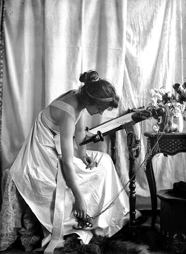 Mise en scène d'un modèle féminin, intérieur : jeune femme assise habillée à la manière antique faisant de la tapisserie, de profil, retenant la laine qui tombe