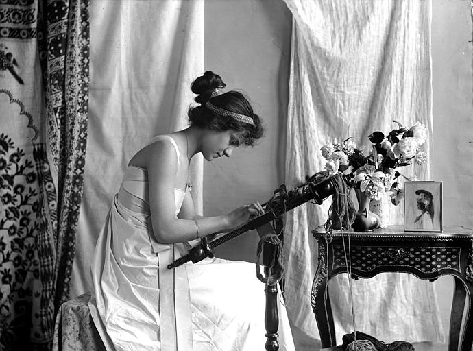 'La Tapisserie', mise en scène présentant une jeune femme assise habillée à la manière antique faisant de la tapisserie, de profil, cousant