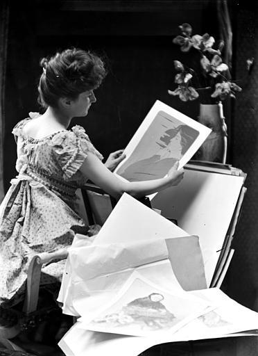 Mise en scène d'un modèle féminin, intérieur : jeune femme de trois-quart dos regardant des estampes de style art nouveau