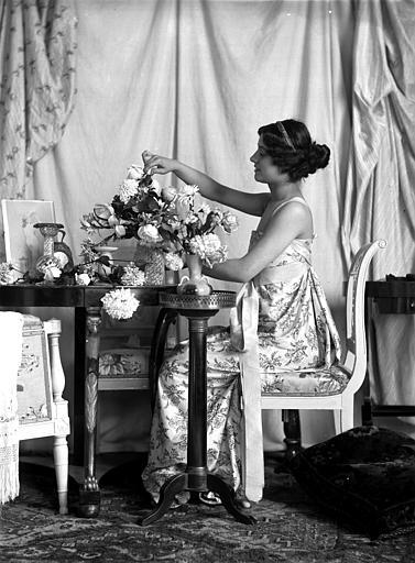 Mise en scène d'un modèle féminin, intérieur : jeune femme de profil, assise à une table, arrangeant un bouquet de fleurs