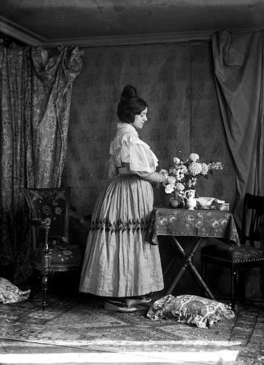 Mise en scène d'un modèle féminin, intérieur : jeune femme de profil, habillée à la manière du style Louis-Philippe, debout à côté d'une table, arrangeant un bouquet de fleurs